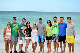 10 members of a white family wearing summer attire standing on a beach with turquoise water in the background.