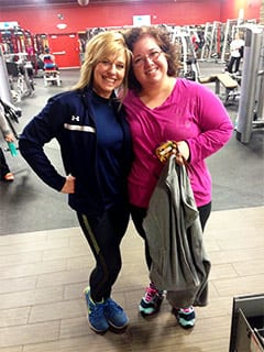 2 women, 1 blonde, middle-aged with dark clothes on left and 1 slightly overweight woman on right with purplish-pink shirt posing together and smiling in a gym.