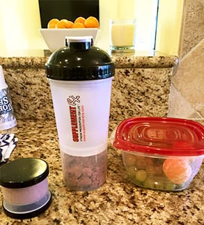Properly portioned healthy food in plastic containers with a shaker bottle.