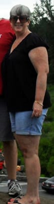 Older overweight woman in a white shirt and black pants.