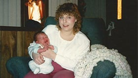 Overweight woman with curly hairsitting on green recliner holding a baby.