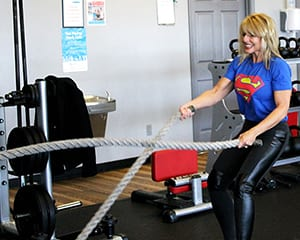 Fit, middle-aged blonde woman wearing a 'Superman' shirt and black pants working the ropes.