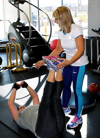 Blonde haired woman working holding sneakered feet of client in grey shirt performing dead bug exercise.